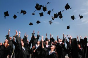 A crowd of graduates throwing their caps in the air.