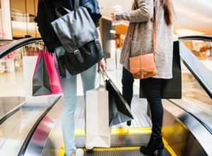 2 people with shopping bags on escalator.