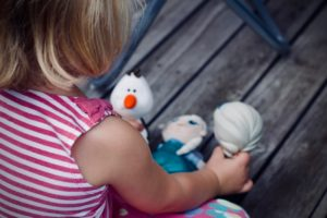 A girl playing with Disney toys.