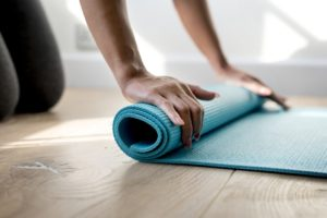 A woman rolling up a yoga mat