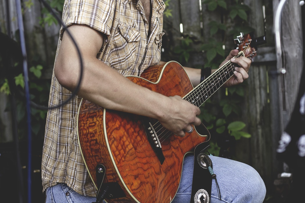 A man playing guitar outside.